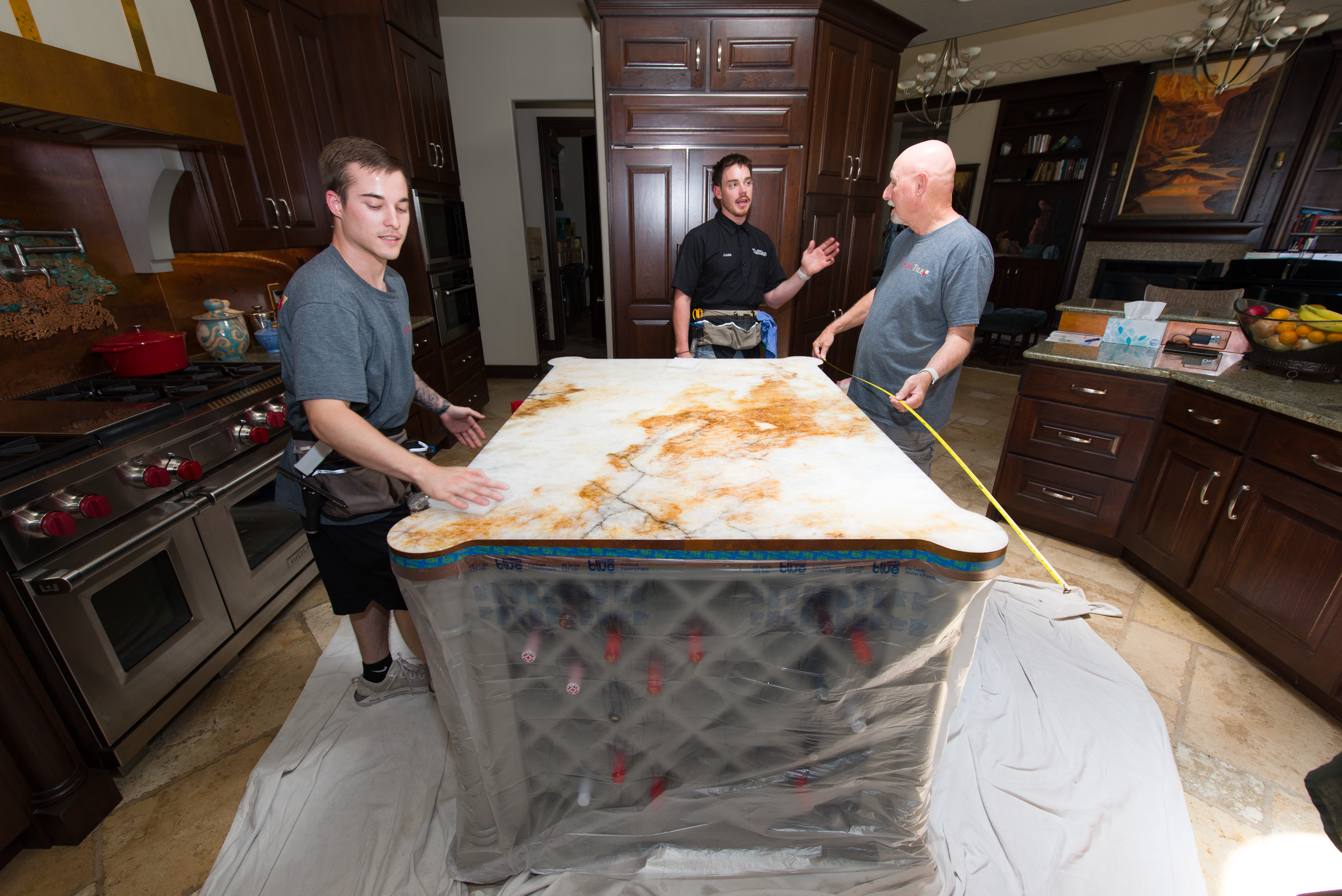 The area is draped and the cabinetry is covered with plastic for protection from water.