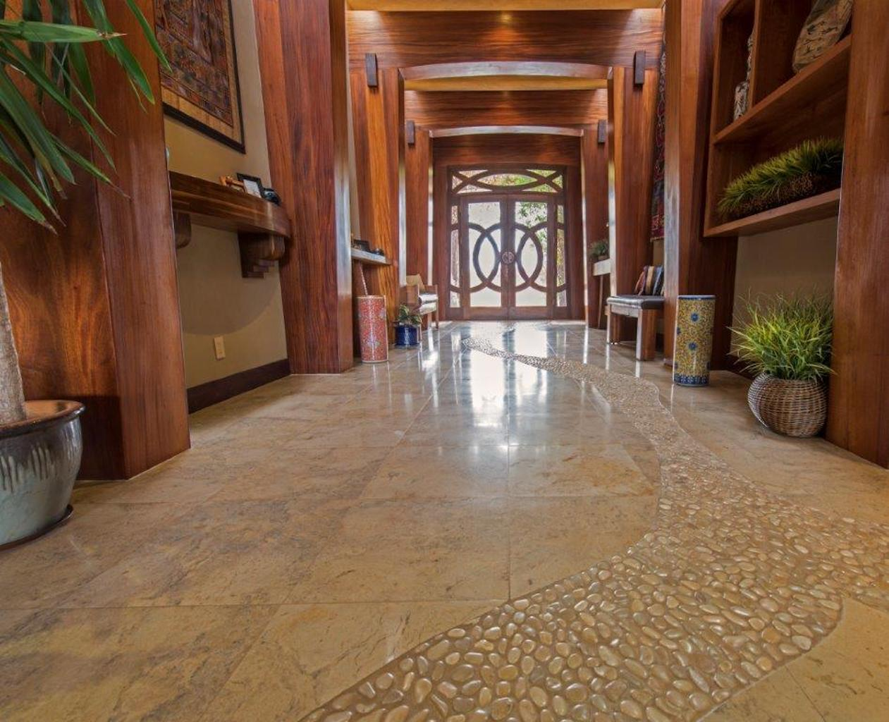 A mixture of travertine and pebbles create a dramatic entrance